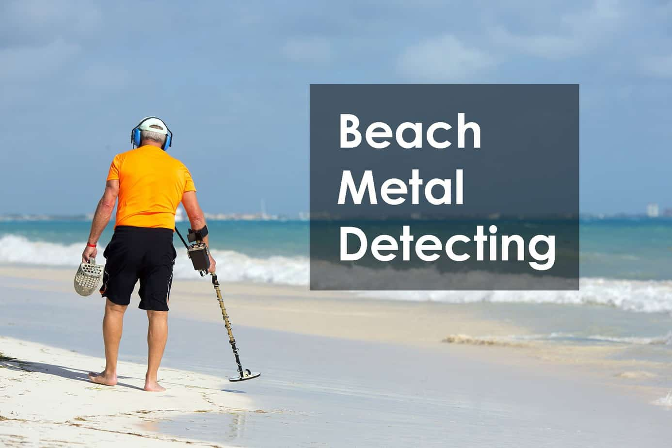 man in yellow shirt on the beach metal detecting